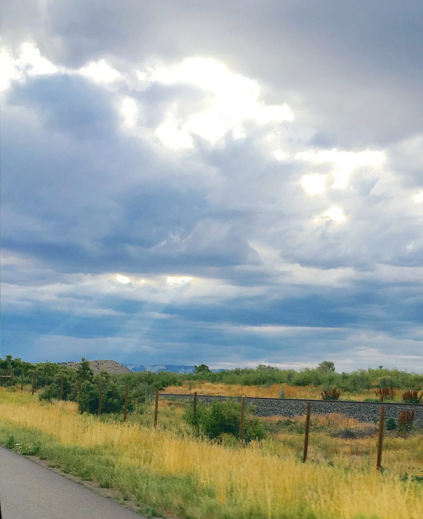 Stormy skies over Colorado with rays of sunlight poking through give for an epic view while traveling around beautiful America
