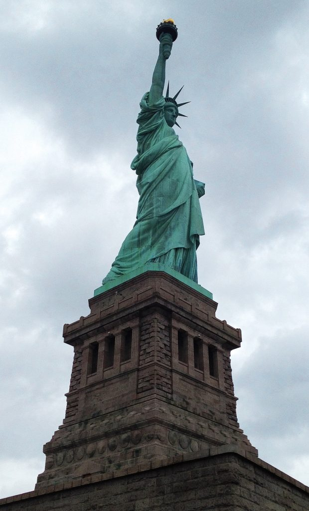 The statue of liberty standing tall in New York Harbor, a top moment  while traveling around beautiful America